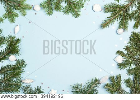 Christmas Fir Tree Branches With White Baubles And Copy Space On A Blue Background. Christmas Green