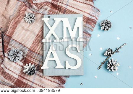 Top-down Winter Holidays Composition With Book, Plaid, Cones And Title On A Blue Background.
