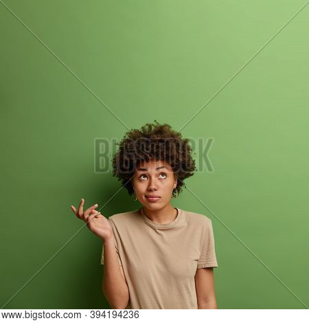 Vertical Shot Of Afro American Woman Has No Idea, Looks Clueless, Raises Palm In Hesitation, Puzzled