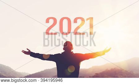 Man Raise Hand Up On Sunset Sky At Top Of Mountain And Number 2021 Abstract Background. Happy New Ye