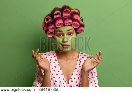 Close Up Portrait Of Hesitant Young Female Model Spreads Hands With Confused Expression, Wears Dress