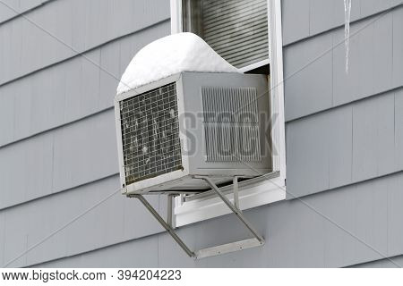Old Air Conditioner Installed On House Window With Snow On Top