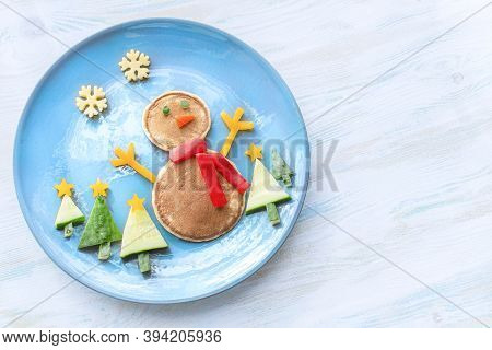 Christmas Pancake Shaped Like A Snowman With Fresh Vegetables Blue Plate On Wooden White Table. Chri