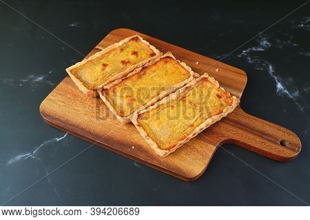 Three Delectable Pumpkin Tartlets On The Wooden Breadboard Isolated On Black Kitchen Table