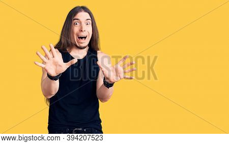 Young adult man with long hair wearing goth style with black clothes afraid and terrified with fear expression stop gesture with hands, shouting in shock. panic concept.