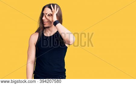 Young adult man with long hair wearing goth style with black clothes doing ok gesture with hand smiling, eye looking through fingers with happy face.