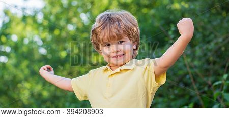 Smiling Child Boy. Cheerful Cheerful Kid. Happy Children Kid Boy With Hands Up. Child Outdoors In Na