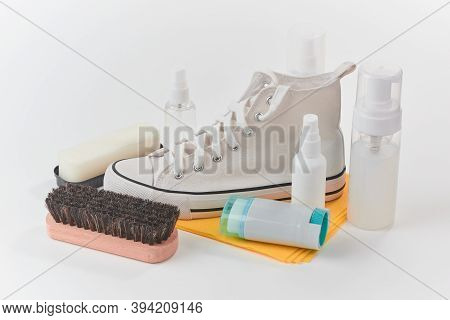 Clean Canvas Sneaker, Brush, Sponge And Various Detergents On White Background