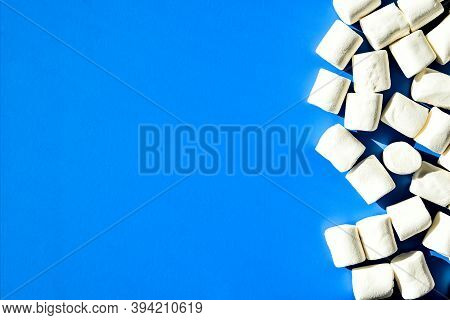 Marshmallows On Blue Background With Copy Space. Flat Lay. Top View. Background Or Texture Of Colorf