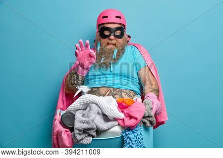 Busy Superhero Looks With Disguise At Camera Holds Basin Of Laundry And Cleaning Products Does House