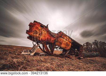 Burnt Wreck Of An Old Car In An Autumn Meadow