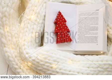 Winter Books. Reading In The Winter Holidays.open Book With Red Christmas Tree On White Knitted Scar