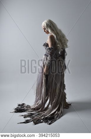 full length portrait of pretty blonde woman wearing torn bridal gown. Standing pose with back to the