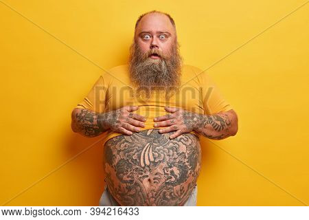 Shocked Amazed Hipster Man Keeps Hands On Belly With Tattoo Sticking Out From T Shirt, Surprised To