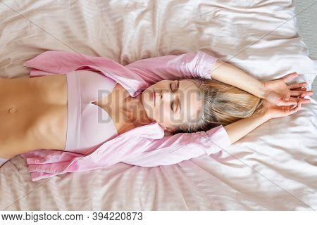 Portrait Of A Cheerful Woman Stretching On The Bed. Pink Pajamas And Brassiere.