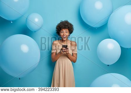 Positive Glad African American Woman Holds Mobile Phone In Hands And Happy To Chat With Friends In S
