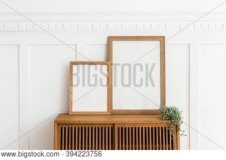 Two picture frames on a wooden sideboard