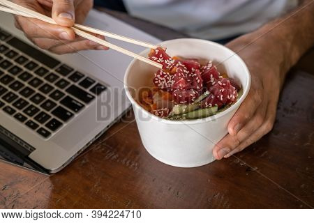Busy Young Man In Casual Wear Sitting At Desk With A Laptop At Home Or In The Office And Eating Heal