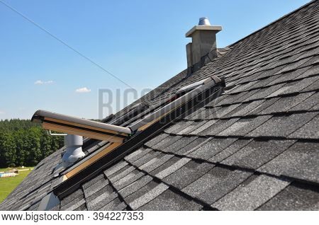 A Gray Roof Covered With Dimensional Architectural Asphalt Shingles With An Attic Skylight, Ventilat