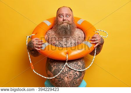 Summer Rest And Safe Swimming Concept. Shocked Bearded Stout Man Stands Naked, Has Tattooed Body And