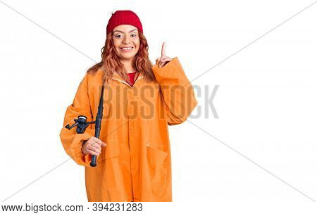 Young latin woman wearing fisher raicoat holding rod surprised with an idea or question pointing finger with happy face, number one