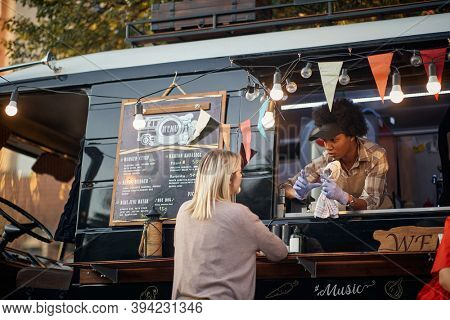 afro-american employee showing size of a fast food mealto a caucasian customer from a window of modified truck for mobile fast food