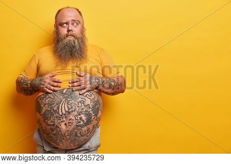 Photo Of Overweight Pensive Man Keeps Hands On Big Belly With Tattoo, Thinks And Looks Aside, Has Th