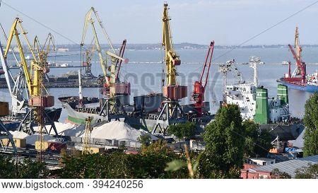 Bulk Carrier Ship Under Load Of Clinker Cargo Loading By Shore Cranes With Grabs. Bulk Cargo Termina