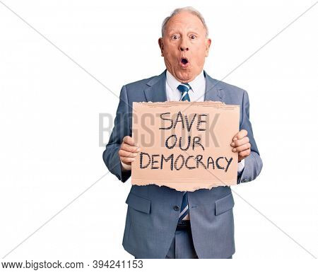 Senior handsome grey-haired man holding save our democracy cardboard banner scared and amazed with open mouth for surprise, disbelief face
