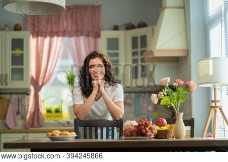 Beautiful brunette woman housewife in white t-shirt and jeans at home in the interior in the kitchen