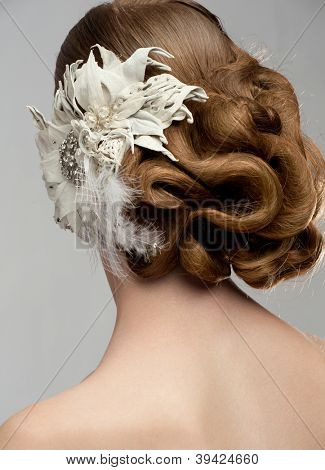 Portrait of attractive young woman with beautiful hairstyle and stylish hair decoration. Bride with gorgeous hairdo