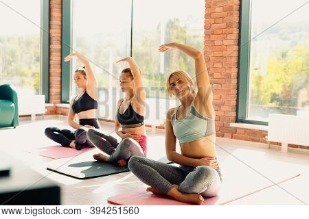 Three Women Do Yoga With An Instructor In A Spacious Gym With Large Windows. Workout, Studio Backgro