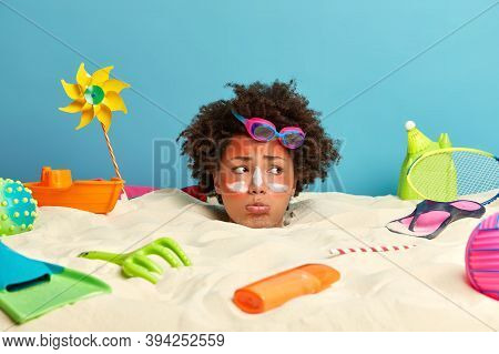Sun Protection And Summer Vacation Concept. Displeased Womans Face Sticks Out From Sand With Applied