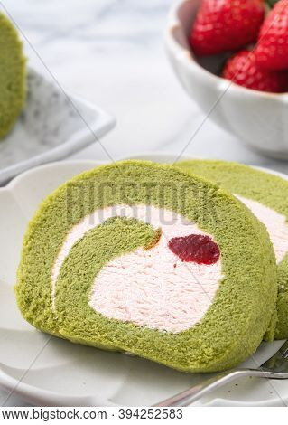 Delicious Matcha Swiss Roll Cake Slices With Strawberry Cream On White Background.