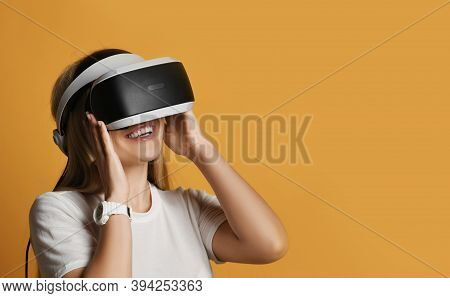 Young Smiling Excited Blonde Woman In White T-shirt Has Fun Using Virtual Reality Wearing Vr Glasses