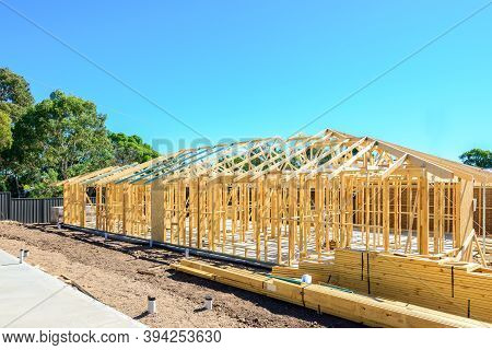 New Australian House Timber Frame Installation Process At Construction Site On A Bright Summer Day