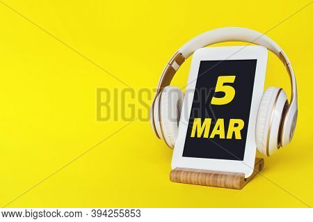 March 5th. Day 5 Of Month, Calendar Date. Stylish Headphones And Modern Tablet On Yellow Background.