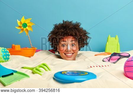 Positive Woman With Afro Bushy Hair, Half Buried In Beach Sand, Got Sunburn On Face, Red Skin, Puts
