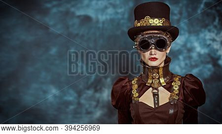Portrait of a beautiful victorian steampunk lady on a grunge background. Fantasy world, scientific inventions. Copy space.