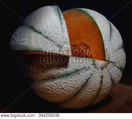 Very Beautiful Melonvery Beautiful Melon With Cut Piece. Melon On A Dark Background. With Cut Piece.