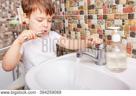 Close-up Of Boy Brushing Teeth With Toothbrush. Happy Child Brushing His Little Teeth In Bath Room.