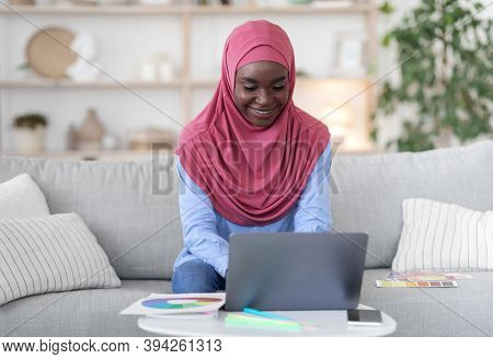 Online Design Courses. African Muslim Lady In Hijab Studying With Laptop At Home, Watching Education