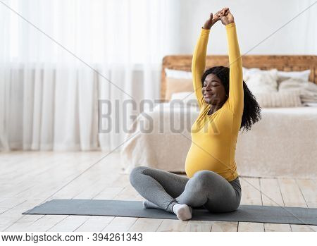 Happy Black Pregnant Lady Stretching Her Body At Home, Sitting On Fitness Mat In Bedroom, Copy Space