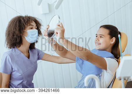 Good Procedure And Snow-white Smile. Happy Small Girl Looks In Mirror For Estimating Dentist Work An