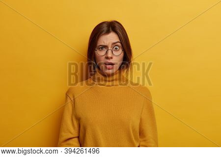 Indignant Puzzled Young Woman Raises Eyebrows And Looks With Shocked Expression At Camera, Hears Sho