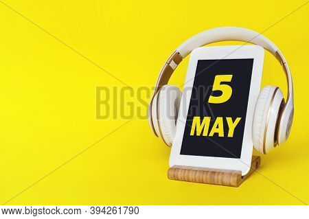 May 5th. Day 5 Of Month, Calendar Date. Stylish Headphones And Modern Tablet On Yellow Background. S