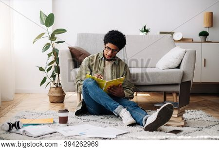 Web Based Education. Busy Black Teen Guy Taking Notes During Online Lecture On Laptop At Home. Focus