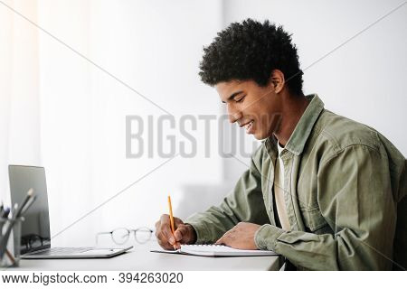 Web-based Training Concept. Black Male Student Writing In Notebook In Front Of Laptop At Home, Empty
