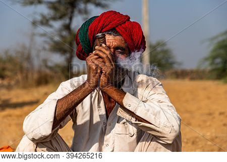 November 2019 Pushkar,rajasthan,india Portrait Of A Man With Red Traditional Turban Smoking Chilam A
