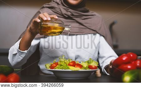 Muslim Lady Cooking Drizzling Olive Oil On Vegetable Salad Preparing Healthy Dinner In Modern Kitche